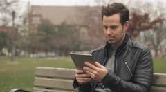 Male Using Tablet Vertically while Sitting on Park Bench in City. Stock Footage