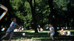 1954: Boys practicing softball swings in shady summer park. Stock Footage