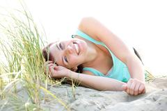 Carefree young woman lying on beach - stock photo