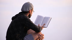Guy reading a book on a rock Stock Footage