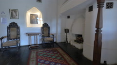 Room with a fireplace and two medieval chairs at Bran Castle Stock Footage