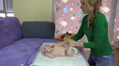 Mother exercise newborn baby in diapers on sofa. 4K Stock Footage