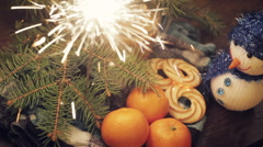 Tangerines and cinnamon stick, lit sparkler on vintage wooden background - stock footage