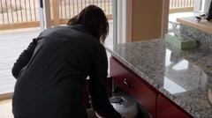 Gimbal shot of a woman putting away dishes in kitchen Stock Footage