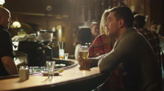 Man sitting alone with beer in a bar while people are having good time Stock Footage