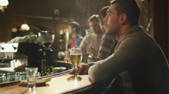 Timelapse footage of a man sitting alone with beer in a bar - stock footage