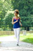 Healthy young woman running outdoors - stock photo