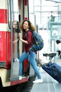 Smiling young woman entering train Stock Photos