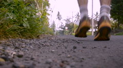Stock Video Footage of Slow motion of a man running away low angle ground view