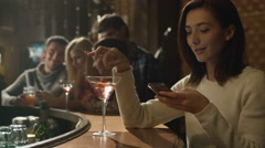 Attractive caucasian woman with a cocktail is using a smartphone in a bar - stock footage