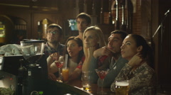 Friends are sitting with drinks and watching a sports game in a bar - stock footage
