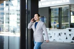 Man exiting building with mobile phone Stock Photos