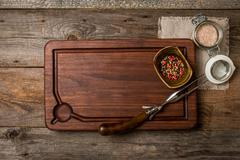Cutting board, seasonings and meat fork - stock photo