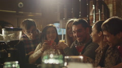 Friends drink beer and cocktails while having a good time together at a bar - stock footage