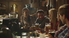 Friends do toasts, drink beer and cocktails while having a good time together - stock footage
