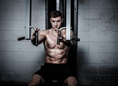 Stock Photo of Athletic man doing exercises on training apparatus at the gym's studio