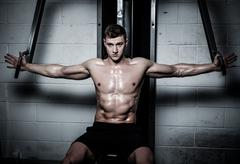 Athletic man doing exercises on training apparatus at the gym's studio Stock Photos