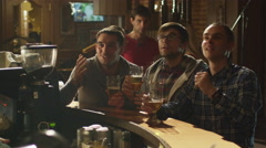 Friends are watching a sports game in a bar and cheering at a score - stock footage