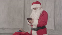Santa claus with tablet pc computer checking gift bag Stock Footage