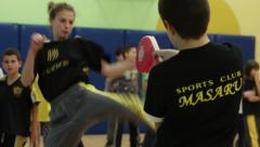 Childrens training in martial arts - the girls are hitting a paw jumping - stock footage