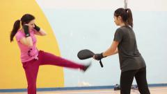 Womens training in martial arts - the girls work out jumps and punches Stock Footage