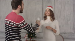 Couple holding champagne while dancing at Christmas party - stock footage
