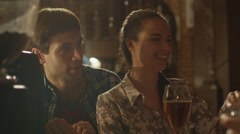 Friends laugh, drink beer while having a good time together at a bar - stock footage