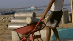 A man brings scuba tanks down to the ocean prepping for divers Stock Footage