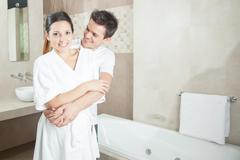 Man and woman hugging in bathroom - stock photo