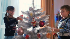 Brother and sister decorating Christmas tree - stock footage