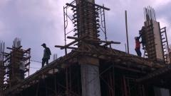 Static silhouettes of construction workers on a building at dusk Stock Footage