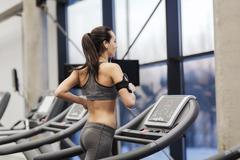 Woman with earphones exercising on treadmill Stock Photos