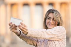 Making a selfie with arms raised - stock photo