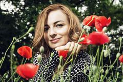 Young caucasian smiling woman with corn poppy flowers, beauty and nature - stock photo