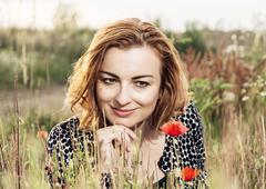 Beautiful caucasian woman is smiling and posing in poppy flowers field Stock Photos