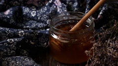 Open glass jar of liquid honey with honeycomb and honey dipper inside, bunch of - stock footage
