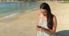 Young caucasian woman texting cell phone on a beach - stock footage
