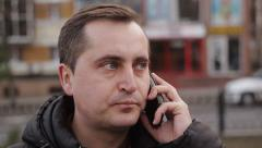 a man interested in talking on the phone outdoors in autumn - stock footage