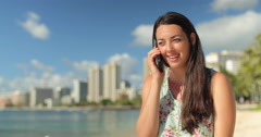 Young caucasian woman talking on cell phone in Hawaii on lawn - stock footage