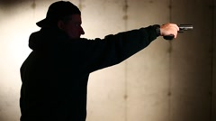 MAN IN PROFILE USES ONE HAND TO FIRE GUN - stock footage