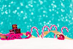 Christmas sledge and candy in snow on glitter background Stock Photos