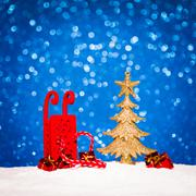 christmas tree and candy in snow on blue glitter background - stock photo