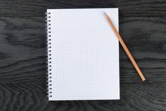 blank notepad with chequered pages on gray wood table with pencil - stock photo