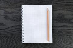 Blank notepad with chequered pages on gray wood table with pencil Stock Photos