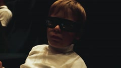 A boy is sitting in the cinema watching a movie with 3d glasses Stock Footage