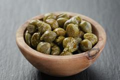 marinated capers in olive bowl on slate board - stock photo