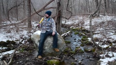 Lumberjack Sits by a Stream - stock footage