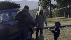 Mom And Dad Put Christmas Tree On Top Of Car, Little Boy Helps, Gives Dad Rope Stock Footage