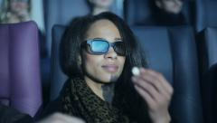 African american young woman is watching 3d cinema and eating popcorn Stock Footage
