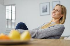 Happy gorgeous young woman sitting daydreaming - stock photo